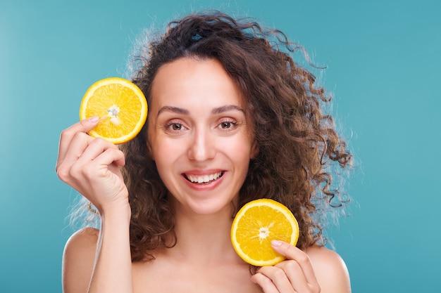 Радостная женщина с зубастой улыбкой и темными длинными волнистыми волосами держит у лица два ломтика свежего сочного апельсина на синем
