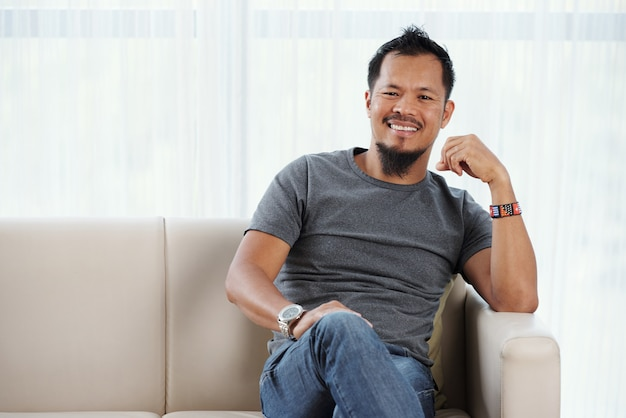 Joyful filipino man seated on couch smiling contentedly at camera