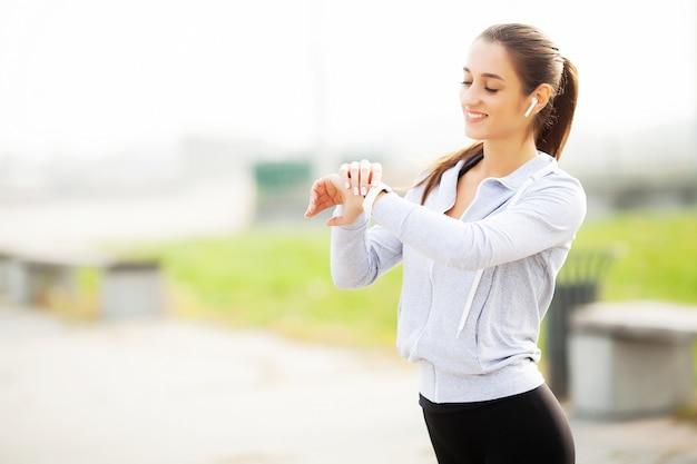 Фотография joyful fitness woman 30s в спортивной одежде, касающейся наушника bluetooth и держащего мобильный телефон во время отдыха в грин-парке