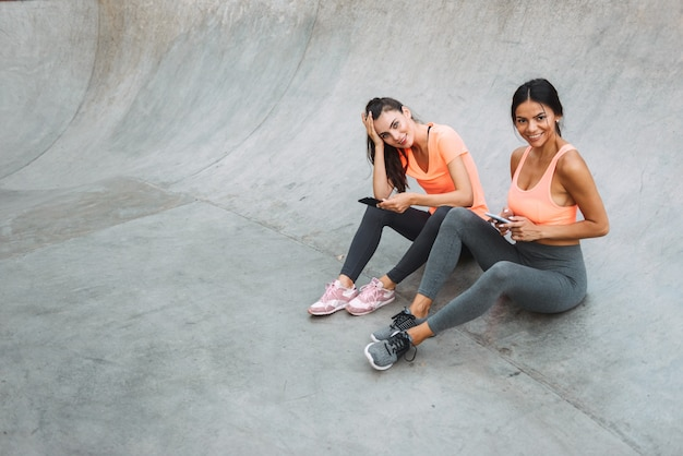 콘크리트 운동장에 앉아있는 동안 미소하고 핸드폰을 함께 들고 운동복에 즐거운 피트니스 여성