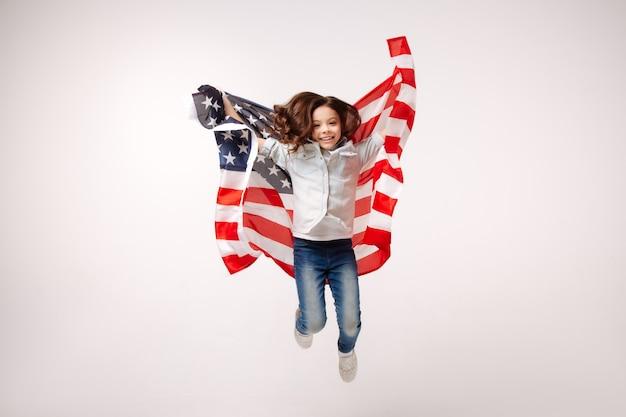 Радостная гибкая улыбающаяся девушка веселится и выражает радость, прыгая против белой стены и держа американский флаг