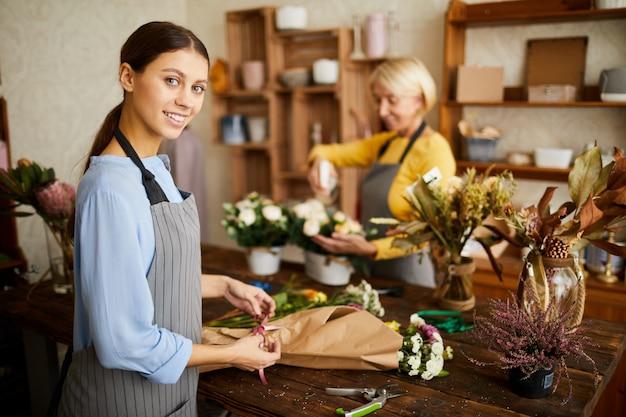 Joyful florist making bouquets