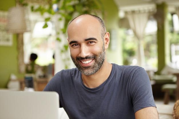 즐거운 프리랜서는 노트북 앞에 앉아 캐주얼 티셔츠를 입고 성공적인 아침 작업 후 쾌활한 표정으로 웃고 야외 카페에서 화창한 날을 즐기고 있습니다.