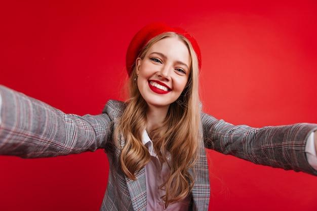 셀카를 복용하는 긴 머리를 가진 즐거운 프랑스 소녀. 붉은 벽에 고립 된 베 레 모에 good-humoured 금발 아가씨.