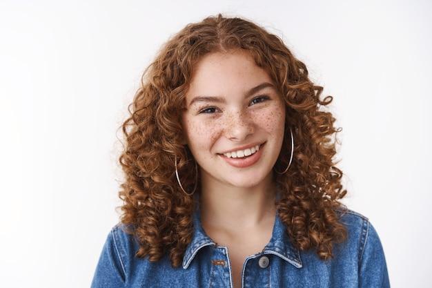 うれしそうなフレンドリーな見た目の若い20代の女子学生の巻き毛のそばかすにきび額が広く話しているあなたがカメラを喜んで見ているように見える、化粧をしないで立っている白い背景デニム