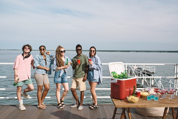Joyful friends arranging small party on wooden pier with drinks and snacks