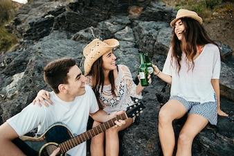 Joyful friends at the beach with guitar