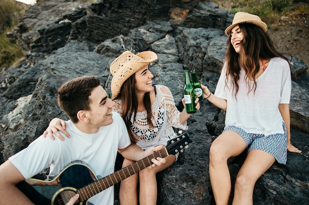 Joyful friends at the beach with guitar