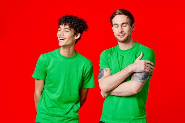 緑の t シャツを着たうれしそうな友達が赤い背景の隣に立っている