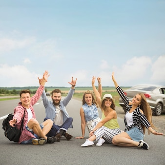 Joyful friends sitting on road raising their hands gesturing