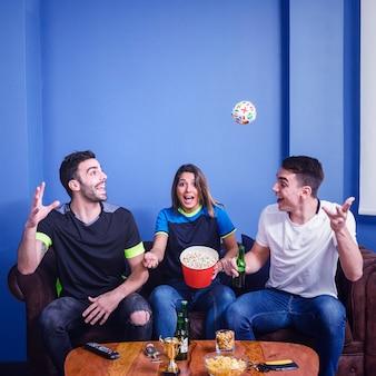 Joyful friends watching football