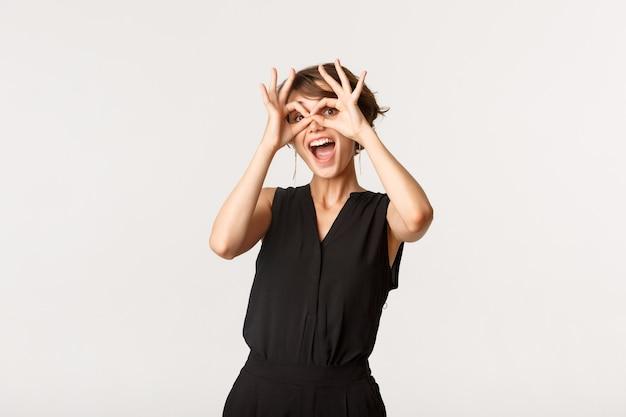 Радостная смешная девушка показывает руки очки и улыбается изумленно, стоя белым.