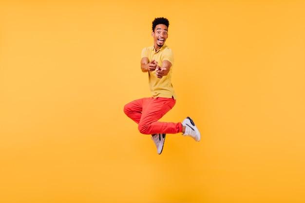 ジャンプする白いスニーカーのうれしそうな面白い男。笑っているアクティブなアフリカ人の屋内写真。