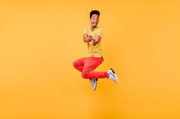 Joyful funny guy in white sneakers jumping. indoor photo of laughing active african man.