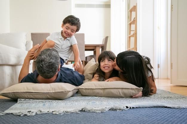 うれしそうな面白い親が寄り添い、抱き合ったり、小さな子供にキスしたり、一緒に楽しんだり