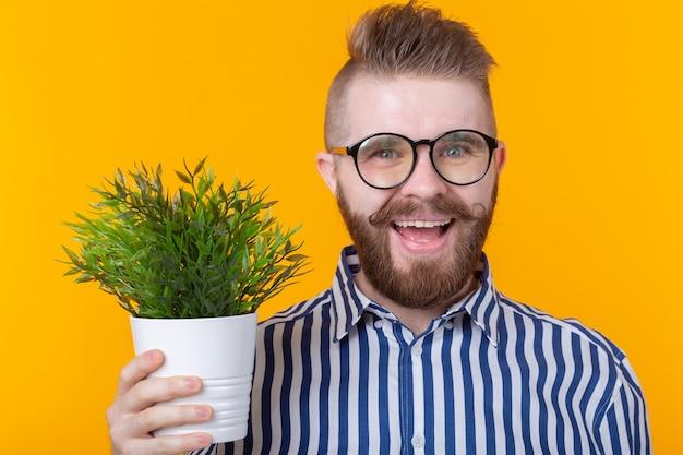 黄色の壁に植物と鍋を保持しているうれしそうな面白い若い男
