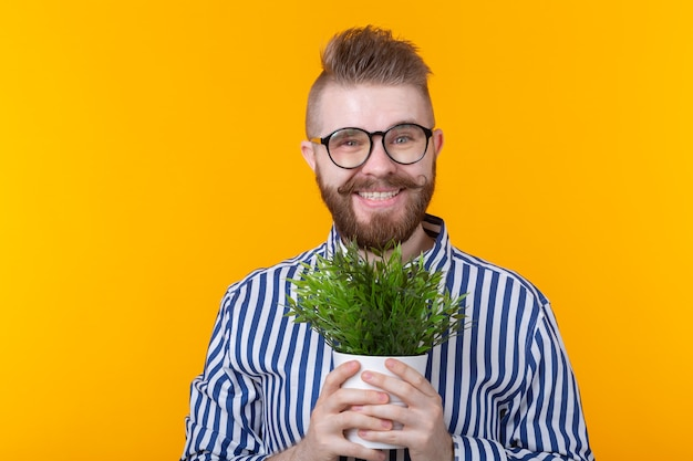 Радостный смешной молодой человек держит горшок с растениями