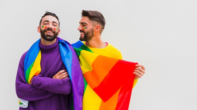 Joyful gay sweethearts holding lgbt rainbow flag
