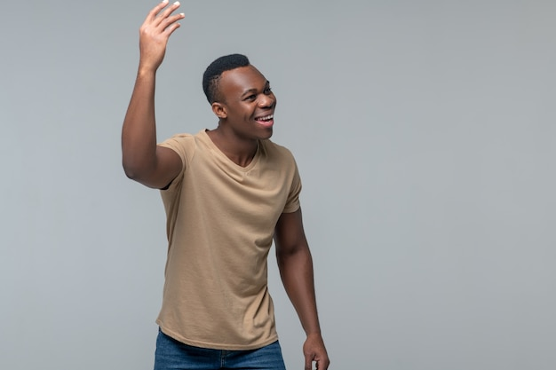 Joyful gesture. smiling rejoicing dark skinned man raising his hand up looking to side on light background