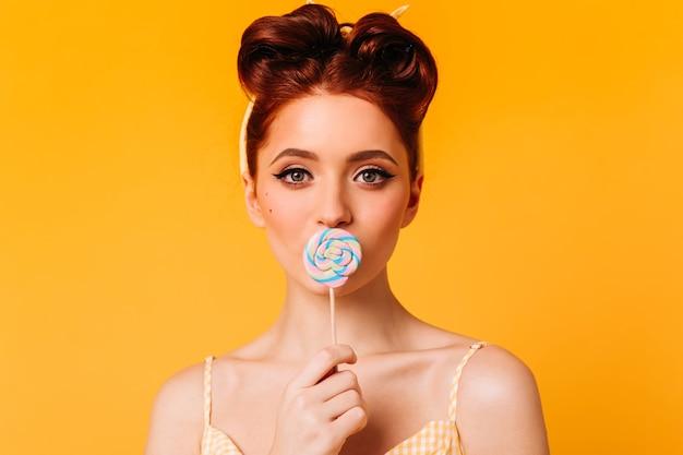 롤리팝을 핥는 즐거운 생강 여자. 노란색 공간에 하드 캔디와 함께 포즈 매력적인 여성 모델.