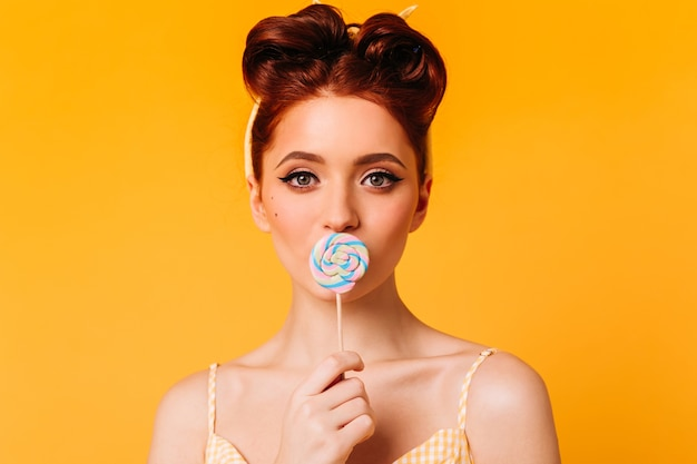 Joyful ginger woman licking lollipop. appealing female model posing with hard candy on yellow space.