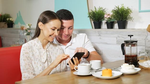 うれしそうな女の子と男は、居心地の良い菓子屋のテーブルの上においしいケーキとお茶と木製のテーブルで現代の携帯電話を見ます