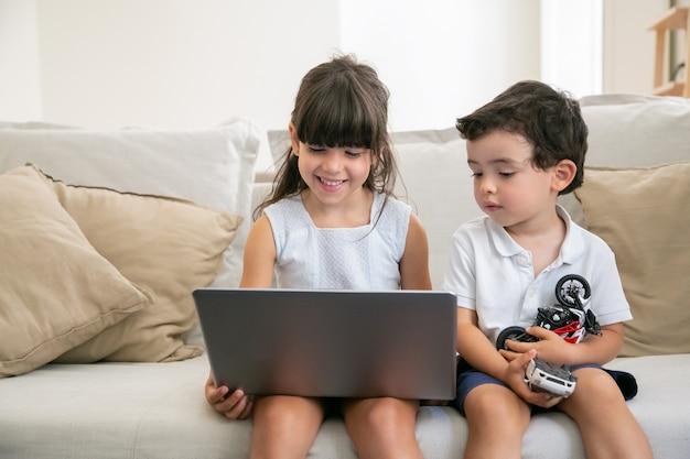 Радостная девочка и ее младший брат сидят на диване у себя дома, используют ноутбук для видеозвонка, онлайн-чата, просмотра видео или фильма.
