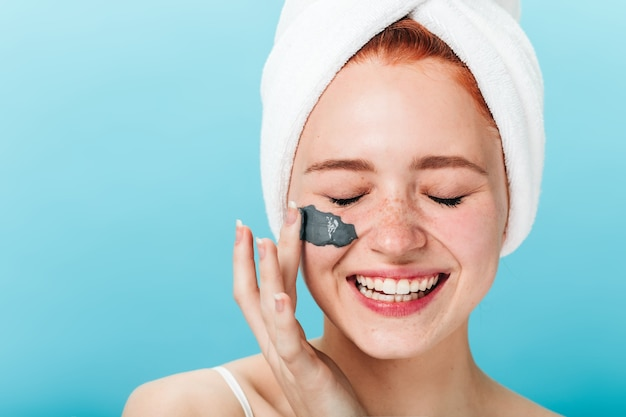 Joyful girl applying face mask with closed eyes. front view of excited lady doing spa treatment isolated on blue background.