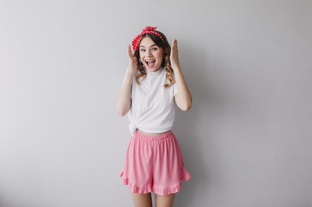 Ragazza allegra in posa divertente pantaloncini rosa carino. foto dell'interno della signora di ispirazione caucasica con i capelli ricci.