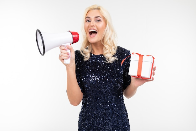 Joyful girl in a dress announces gifts in a megaphone holding a gift box on a white studio background.
