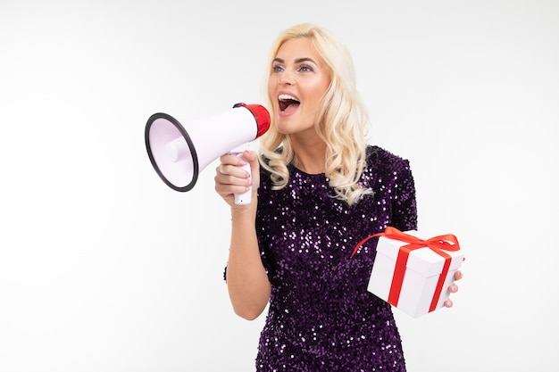 Joyful girl in a dress announces into a loudspeaker about a draw holding a gift box on a white studio background