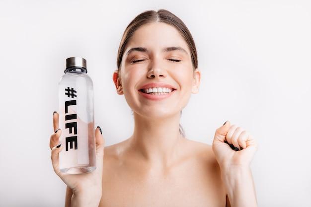 Ragazza allegra di buon umore sorride, in posa con gli occhi chiusi sulla parete isolata. la donna senza trucco tiene la bottiglia d'acqua.