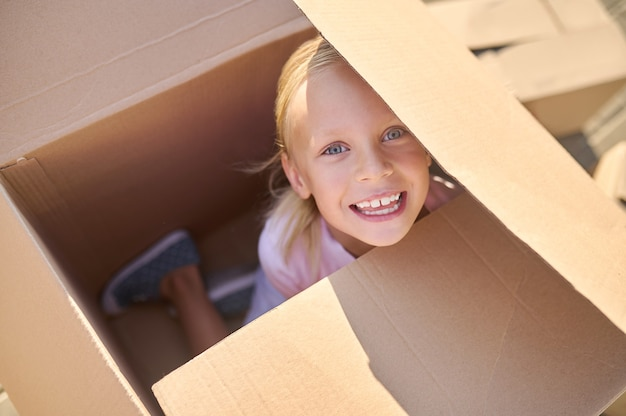 Радостная девушка прячется в большой коробке на улице