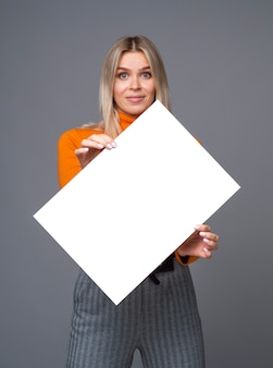 Joyful girl holding a diagonally tilted big paper sheet a1 with copy space for mockup.