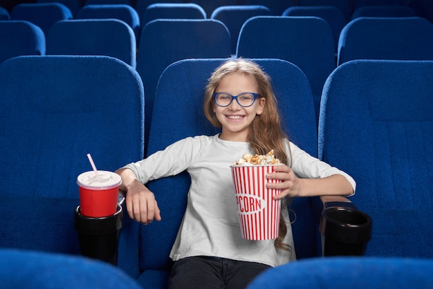 Joyful girl holding popcorn bucket, posing in cinema.