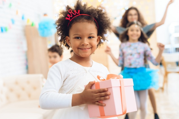 Joyful girl holds gift in pink box at birthday party.