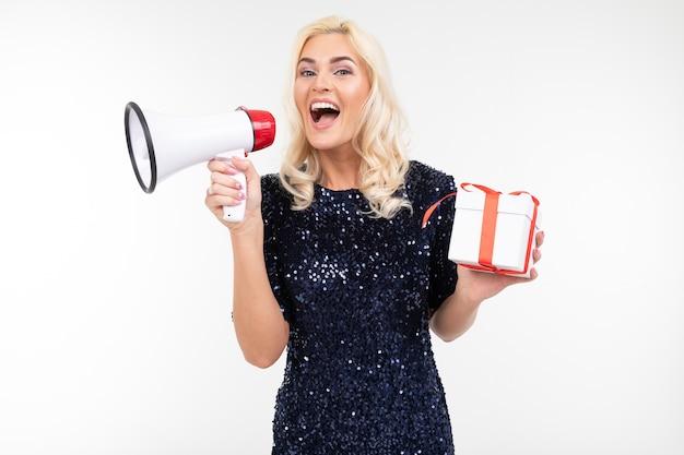 Радостная девушка в платье объявляет о подарках в мегафон, держа подарочную коробку на белом фоне студии.