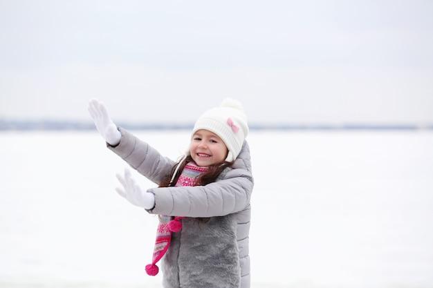 屋外で楽しんでいる美しい暖かい服装のうれしそうな女の子