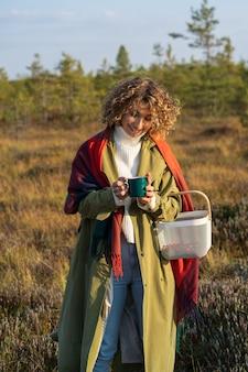 따뜻한 차 한 잔에 따뜻한 손을 얹은 즐거운 소녀는 시골에서 화창한 가을을 즐기며 주말을 보낸다