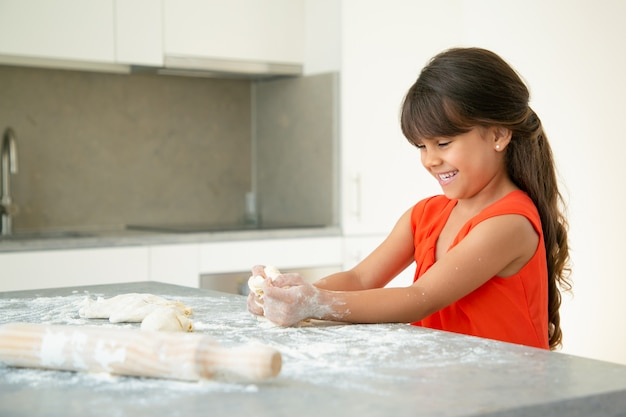 지저분한 밀가루로 식탁에 반죽을 반죽하고 웃고 즐거운 소녀. 혼자서 빵이나 파이를 굽는 아이. 미디엄 샷. 가족 요리 개념