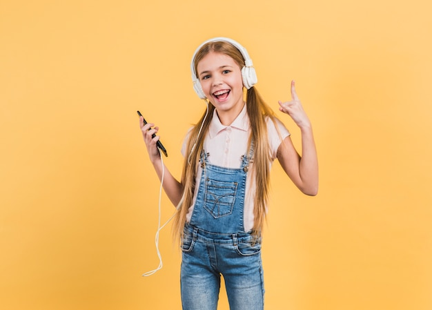 Joyful girl listening music on headphone making rock sign against yellow background