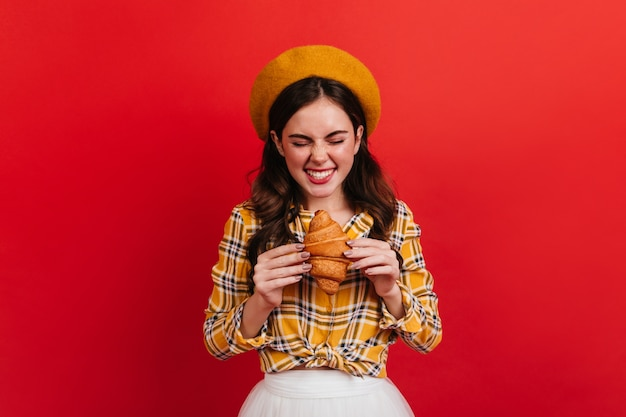Joyful girl looks at freshly baked croissant in anticipation. portrait of lady in orange beret and white skirt on red wall.