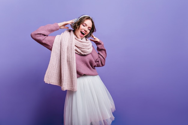 Joyful girl in lush white skirt looking down with inspired smile. refined brunette lady in long warm scarf dreamy posing on purple wall.