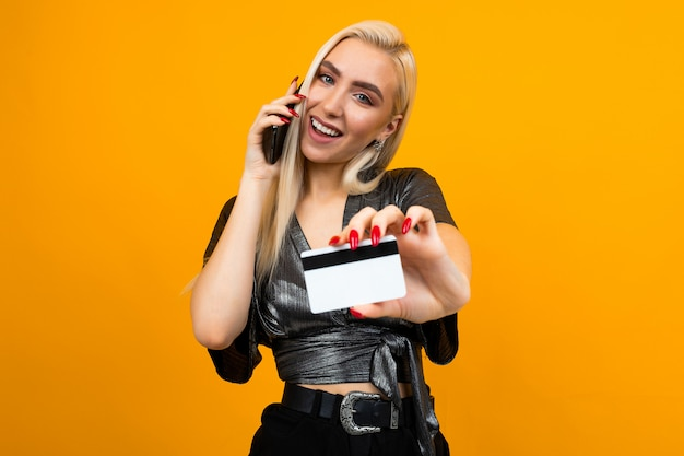 Joyful girl makes purchases by phone holding a credit card with a mockup on a yellow studio background