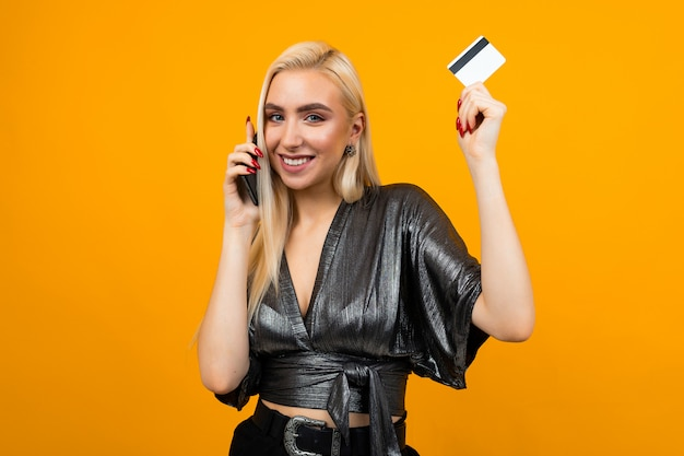 Joyful girl makes purchases by phone holding a credit card with a mockup on yellow wall