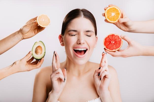 Радостная девушка загадывает желание. портрет модели без макияжа на белой стене с фруктами.