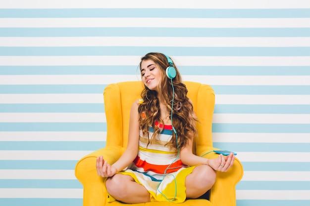 Радостная девушка медитирует, сидя в позе лотоса на синей полосатой стене. довольно молодая женщина в ярком платье отдыхает в желтом кресле и слушает расслабляющую музыку.