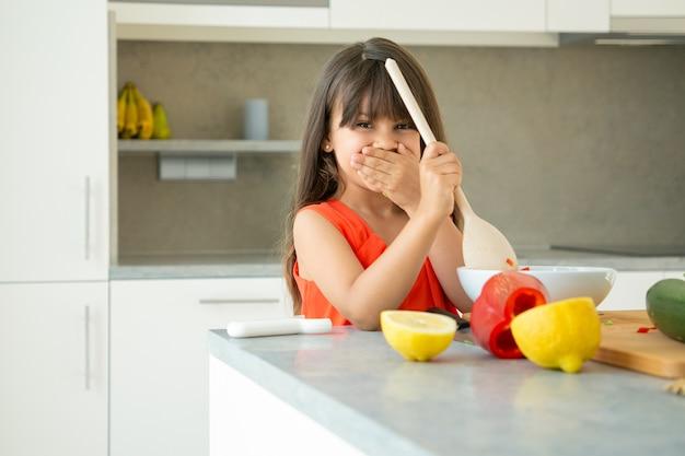 Радостная девушка, бросая салат в миску с большой деревянной ложкой. милый ребенок учится готовить овощи на ужин, позирует, улыбаясь в камеру. обучение приготовлению концепции