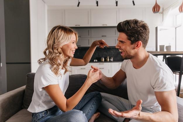 Ragazza allegra che cerca di distrarre il suo ragazzo mentre gioca a casa. il ragazzo divertente discute con la sua ragazza durante il gioco.