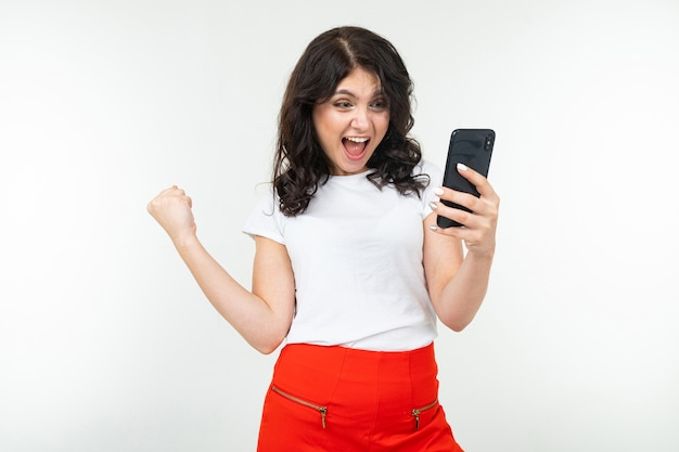 コピースペースと白い背景の上の彼女の手で携帯電話を持つうれしそうな女の子。